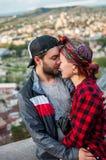 Jeunes paires d'amants sur un fond de ciel bleu et des gratte-ciel à Tbilisi Photographie stock libre de droits