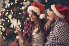 Jeunes paires dans l'amour regardant le téléphone portable ensemble images stock