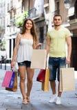 Jeunes paires de sourire avec des paniers à la ville Images stock