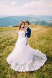 Jeunes paires les épousant romantiques posant sur le champ d'herbe ensoleillé avec Forest Hills éloigné et le ciel merveilleux co Images libres de droits