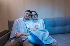 Jeunes paires se blottissant vers le haut de la télévision de observation Images stock
