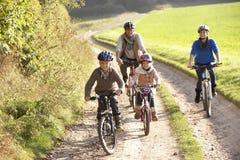 Jeunes parents avec des vélos de conduite d'enfants en stationnement Photos libres de droits