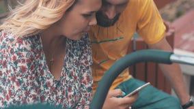 Jeunes parents avec la voiture d'enfant sur le banc Employez le smartphone Famille heureux Été banque de vidéos