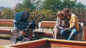 Jeunes parents avec la voiture d'enfant sur le banc Selfie de prise sur le smartphone famille banque de vidéos