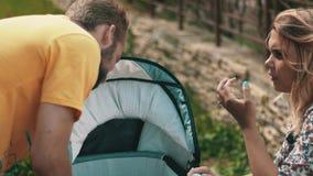 Jeunes parents avec la voiture d'enfant sur le banc Vérification du bébé famille playground banque de vidéos