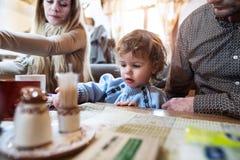 Jeunes parents avec le fils dans le repas de attente de restaurant Images libres de droits