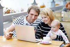 Jeunes parents avec leur bébé doux en café d'extérieur Photos libres de droits