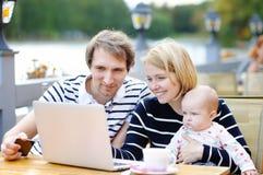 Jeunes parents avec leur bébé en café d'extérieur Photo stock