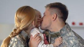 Jeunes parents dans la joue de baiser de fille d'uniforme de camouflage, proximité de famille banque de vidéos