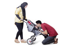 Jeunes parents et bébé dans la poussette Photos stock