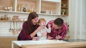 Jeunes parents heureux avec la fille d'enfant en bas âge ayant l'amusement avec de la farine dans la cuisine clips vidéos