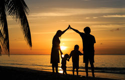 Jeunes parents heureux faisant à la maison pour des enfants au coucher du soleil Photo stock