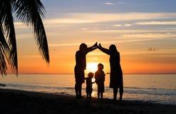 Jeunes parents heureux faisant à la maison pour des enfants au coucher du soleil Photo libre de droits