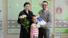 Jeunes parents heureux tenant un bébé nouveau-né, se tenant au seuil de l'hôpital banque de vidéos