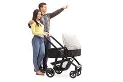 Jeunes parents poussant une poussette de bébé Images stock