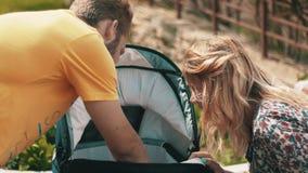 Jeunes parents vérifiant le bébé dans le chariot sur le banc famille playground banque de vidéos