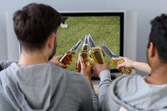 Jeunes passionés du football regardant la rencontre à l'intérieur Photographie stock libre de droits