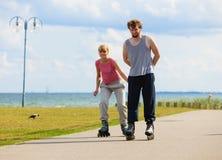 Jeunes patinant ensemble en parc de bord de mer Images stock