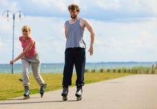 Jeunes patinant ensemble en parc de bord de mer Photos libres de droits