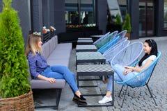 Jeunes personnes féminines s'asseyant au café de rue dehors Photographie stock