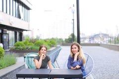 Jeunes personnes féminines s'asseyant au café de rue dehors Images stock