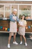 jeunes petits entrepreneurs dans les tabliers se tenant avec les bras croisés et souriant à la caméra image stock