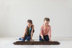 Jeunes plantes de symbole de jour de terre avec des enfants Image libre de droits
