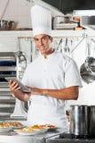 Jeunes plats de pâtes de Holding Tablet With de chef à Photo stock