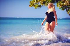 Jeunes plus la femme de taille dans les vêtements de bain appréciant des vacances dans l'éclaboussure de l'eau sur la plage photos libres de droits
