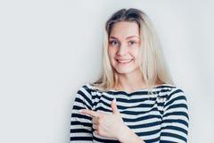 Jeunes points blonds de sourire mignons de femme un doigt loin Présentation de votre produit sur le fond blanc image libre de droits