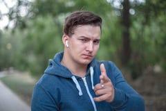 Jeunes points caucasiens d'homme son doigt à la visionneuse images stock