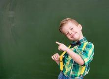 Jeunes points de garçon sur le tableau vert vide Photo libre de droits
