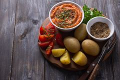 Jeunes pommes vapeur dans une peau avec le caviar de courgette, les épices, les tomates fraîches et le persil Photographie stock libre de droits