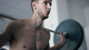 Jeunes postures accroupies de bodybuilder avec un barbell dans un gymnase avec le torse nu banque de vidéos