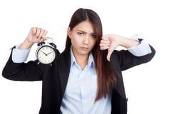 Jeunes pouces asiatiques de femme d'affaires vers le bas avec le réveil Photos stock