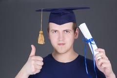 Jeunes pouces d'homme d'obtention du diplôme vers le haut au-dessus de gris Images libres de droits