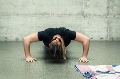 Jeunes pousées attrayantes méconnaissables de fille de forme physique formant la séance d'entraînement sur le plancher de gymnase photographie stock libre de droits