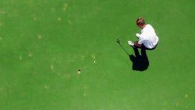 Jeunes pratiques en matière de golfeur sur un cours, frappant une boule dans un trou banque de vidéos