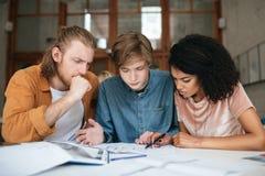 Jeunes réfléchis travaillant dans le bureau Deux garçons avec les cheveux blonds et la fille avec la séance foncée et l'étude de  Photographie stock