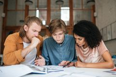 Jeunes réfléchis travaillant dans le bureau Deux garçons avec les cheveux blonds et la fille avec la séance foncée et l'étude de  Photo libre de droits