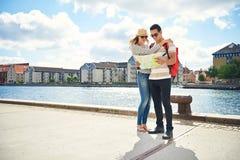 Jeunes randonneurs à la mode consultant une carte Image stock