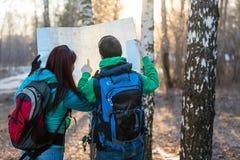 Jeunes randonneurs de couples regardant la carte photographie stock libre de droits