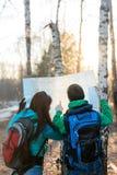 Jeunes randonneurs de couples regardant la carte Image libre de droits