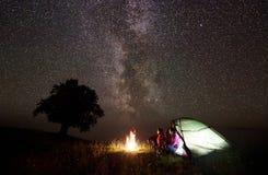 Jeunes randonneurs de couples se reposant près de la tente lumineuse, campant en montagnes la nuit sous le ciel étoilé Images stock