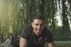 Jeunes rires arabes d'une chevelure noirs d'homme regardant en riant devant lui en parc d'été image stock