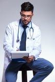 Jeunes séance et écriture de docteur Photos stock
