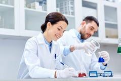 Jeunes scientifiques faisant l'essai ou la recherche dans le laboratoire photos stock