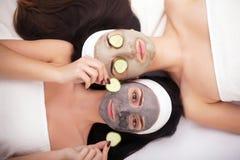 Jeunes soeurs comiques après la douche faisant le masque avec le concombre Photos stock