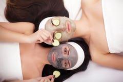 Jeunes soeurs comiques après la douche faisant le masque avec le concombre Image stock