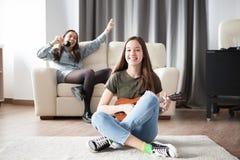 Jeunes soeurs heureuses ayant l'amusement dans le salon Image libre de droits